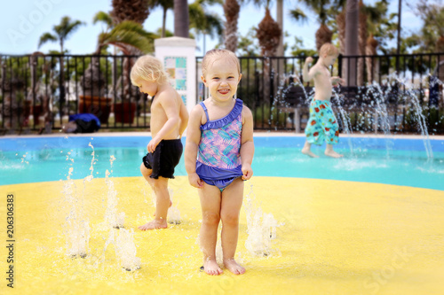 Foto Murales Cute Little Toddler Girl Playing in a Splash Park with Friends Outside on Summer Day