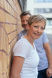 Smiling mature woman leaning against wall