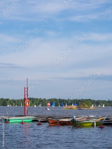 Fotobehang Zeilen Sailing competition and small boats in marina on sunny lake