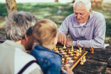Active retired people, old friends and free time, two senior men having fun and playing chess at park, spend time with grandson