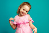 Cute little girl posing in dress ahead isolated blue