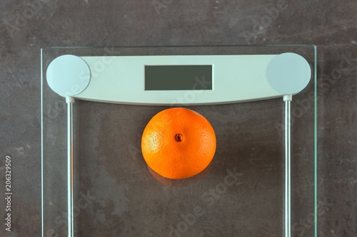 One ripe orange lies on the scales. The concept- weight loss, weight control, anorexia.