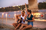 Two young female friends sitting by the river,singing and playing guitar.Joying in summer evening . - 206334945
