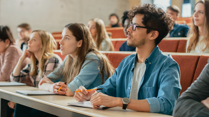 In the Classroom Multi Ethnic Students Listening to a Lecturer and Writing in Notebooks. Smart Young People Study at the College.