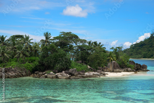 Fotobehang Blauw Beautiful view of one of the islands of Seychelles in the Indian Ocean. On the island lie huge stones. Evergreen vegetation is in the foreground.