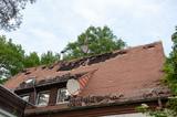 haus mit dachschaden abgedeckten dachziegeln sturm brand feuer unwetter - 206338563