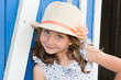 Quadro pretty beauty child girl wearing flower dress and straw hat smiling with wood white and blue hut background