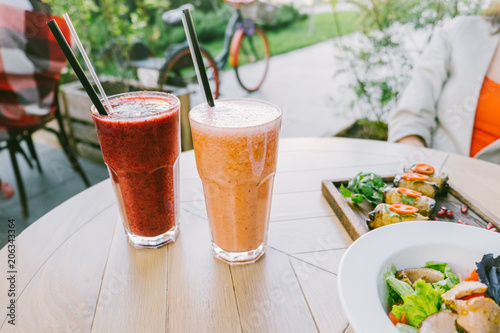 Fototapeta Healthy eating and summer concept. Two glasses of smoothies and snacks on a wooden table of a cafe summer terrace.