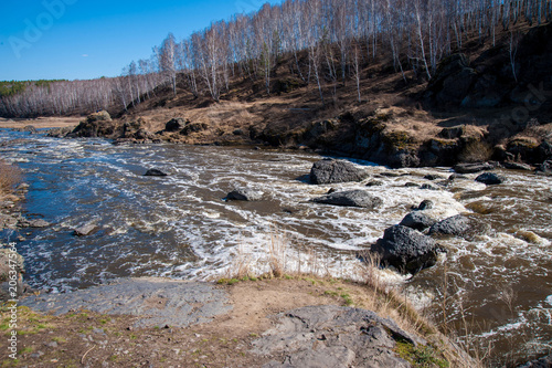 Fotobehang Bergrivier a rough river with rapids in the forest, with splashes of water, under a blue sky, surrounded by forest