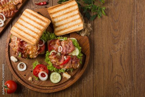 Wall mural Toasted sandwich with bacon, tomato, cucumber and lettuce.
