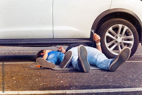 Father and son working under broken car together
