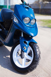 Blue modern scooter on the gravel road front view