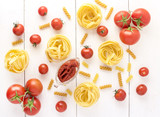 Pasta Products with Tomato Raw Pasta Fusili Fettuccine Ingredients Italian Food White Background Top View Flat lay - 206355567