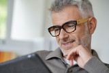 Smiling middle-aged man connected with tablet - 206359389