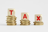 The word Tax written with wood blocks on top of coins piles - Tax decrease concept - 206369315
