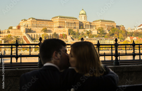 Fotobehang Boedapest Couple in love is kissing and hugging on the wooden bench in the morning city. Man and woman in black clothes are sitting near the Buda castle panoramic view. Ancient city european urban landscape.