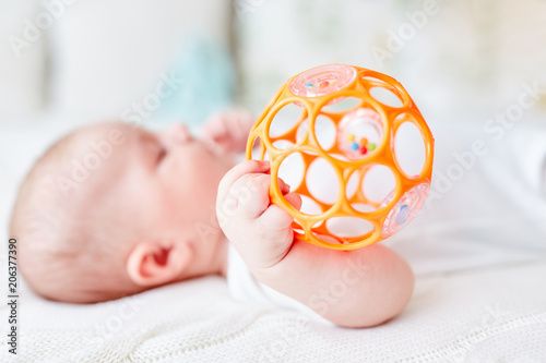 Leinwandbild Motiv Baby greift mit einer Hand die Rassel