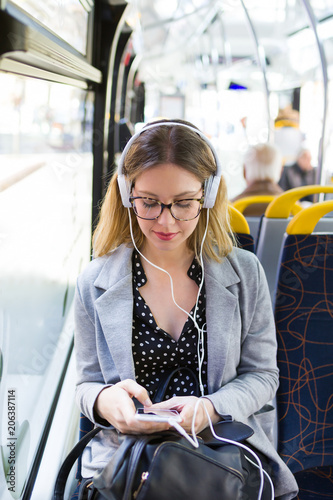 Fototapeta Pretty young woman listening to music with mobile phone at the bus.