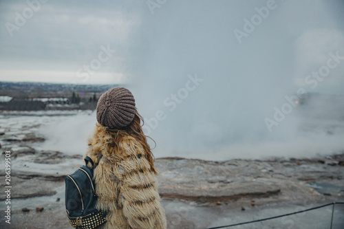 Foto Murales Young woman with fur coat and hat backwards in  Geysir National Park in Iceland