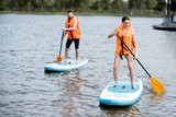 Couple in life vests learning to row on the stand up paddleboard on the lake - 206441369