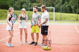 Group of friends having fun standing together with rackets on the tennis court