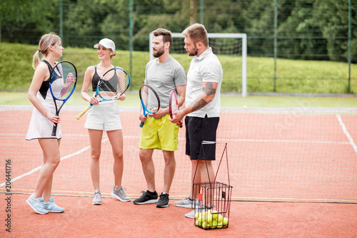 Fotobehang Tennis Group of friends having fun standing together with rackets on the tennis court