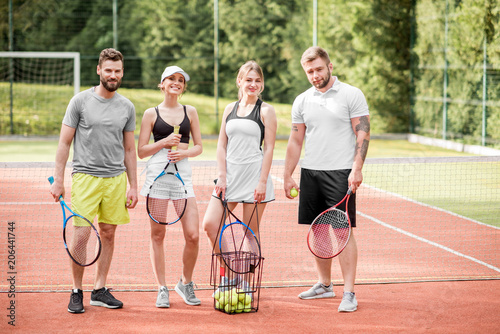 Fototapeta Portrait of a group of young friends in sportswear standing with rackets on the tennis court outdoors