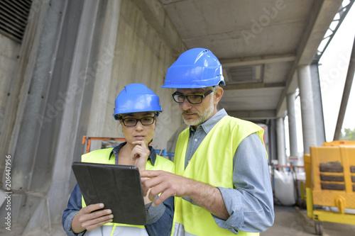 Recycling industry workers using tablet outside factory