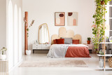 Mirror on cabinet next to orange bed under posters in bright bedroom interior with plants. Real photo - 206459105