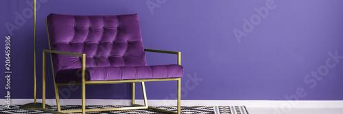 Fioletowy fotel ze złotą metalową ramą stojącą na wzorzystym czarno-białym dywanie w fioletowym wnętrzu czytelni. Umieść swój produkt tutaj