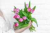 A girl in a nightgown holds a bouquet of delicate pink tulips in the early morning against a white brick wall. - 206461512