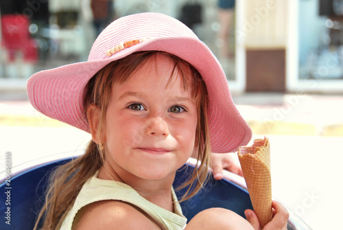 Small girl with hat eat ice cream.