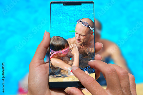 Woman with mobile phone photos small girl with her father in the swimming pool.