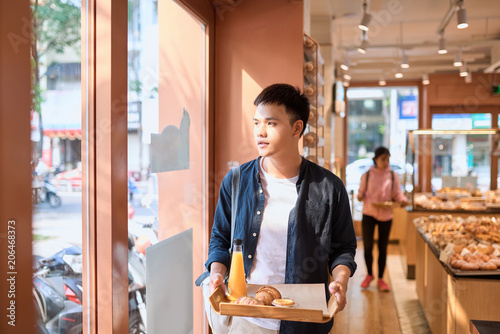Handsome asian man buying bakery for coffee break in the afternoon. Bakery and Coffee break.