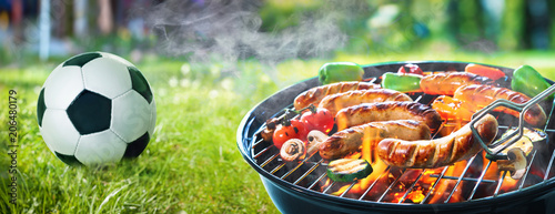 Grilled sausage on the flaming grill and soccer ball - 206480179