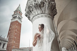 Beautiful bride in long elegant, luxury ivory dress and messy updo hairstyle, covered face by veil, posing near columns in Venice, Italy