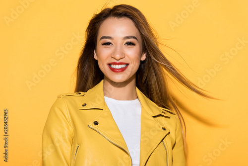 smiling asian female model posing on yellow background