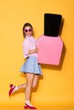 smiling stylish female model in sunglasses holding decorative nail polish on yellow background - 206483791