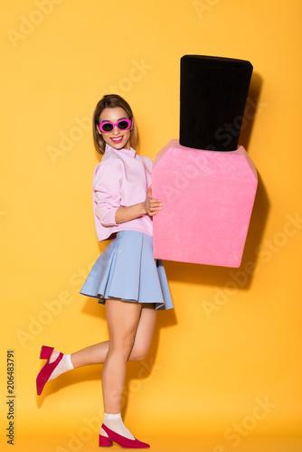 smiling stylish female model in sunglasses holding decorative nail polish on yellow background