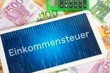 Ein Tablet PC, Euro Geldscheine und die Einkommensteuer