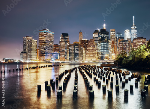 Wall mural Manhattan skyline seen from Brooklyn at night, color toned picture, New York City, USA.