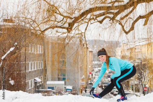 Foto Murales Winter workout. Girl wearing sportswear, stretching exercises.