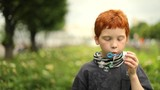 Young boy blowing bubbles in the park, slow motion - 206511351