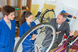 bicycle mechanic and apprentice repairing a bike in workshop - 206515924