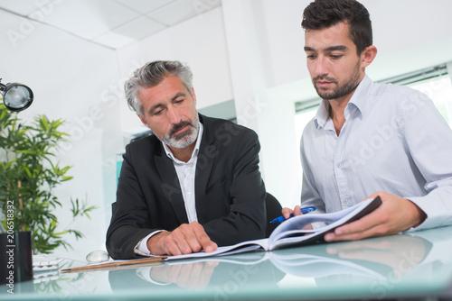 Men in office looking through brochure