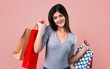 Leinwanddruck Bild - Teenager girl with shopping bag on pink background