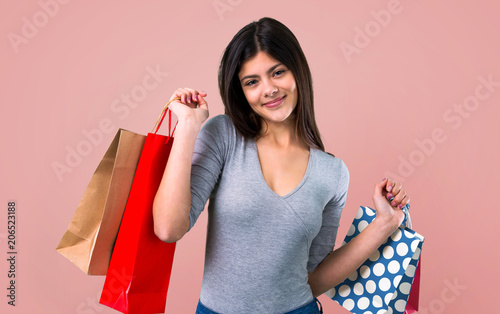 Leinwanddruck Bild Teenager girl with shopping bag on pink background