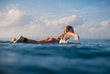 Attractive surf woman rowing on the surfboard. Woman with surfboard in ocean. Surfer and ocean - 206548133