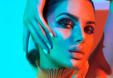 Fashion model woman in colorful bright lights with trendy makeup and manicure posing in studio - 206564367