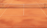 Clay tennis court with net and white markings